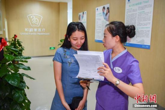 5月30日,25岁的史佳雨女士在接种HPV九价疫苗前与海南博鳌超级医院的护士确定个人信息。当日,备受关注的HPV九价疫苗在海南博鳌超级医院和睦家医疗中心开始注射。来自北京的史佳雨女士接种了中国内地第一针HPV九价疫苗。中新社记者 骆云飞 摄