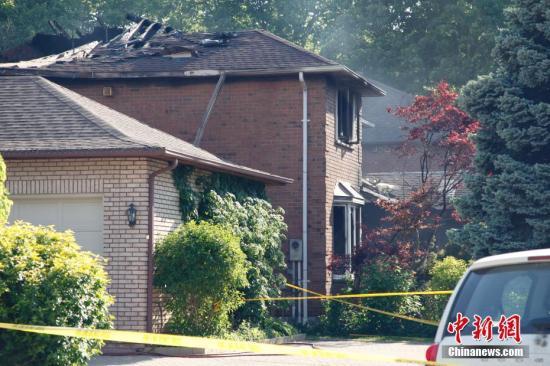 当地时间5月30日凌晨,加拿大多伦多一民宅发生火灾,造成在此租住的多伦多大学士嘉堡校区中国留学生1人死亡、3人受伤。图为当天下午,失火民宅已无明火,但仍有轻微冒烟。可看到屋顶大面积烧塌,二楼的窗户和外墙被明显烧损。该房屋为独立屋,所在小区毗邻多伦多大学士嘉堡校区。目前火灾起因仍在调查之中。中新社记者 余瑞冬 摄