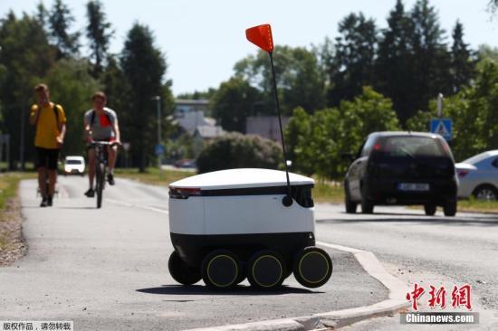 """资料图:当地时间20186月1日,英国智能配送机器人制造商Starship Technologies开发的送货机器人在爱沙尼亚绍埃上路测试。该智能配送机器人能够实现99%的自动操作,这也就意味着它可以自行行驶,不过也需要人工监控和控制,防止机器人""""走失""""。机器人在配送过程中,所携带的包裹都是被严密封锁,接收者只有通过其智能手机才能打开。"""