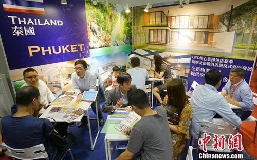 """资料图片:""""SMART国际房地产及投资博览会""""在香港会展中心举行。图为泰国房地产项目参展摊位吸引众多香港市民咨询洽谈。中新社记者 张炜 摄"""