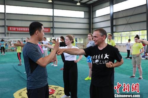 """6月4天,适以广东岭南师范学院参加""""孔子课堂""""夏令营的21号称白俄罗斯师生正跟着老师一招一式学习中国太极拳。中新社发 冯富 拍摄"""