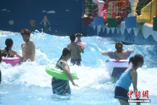 资料图:炎热高温天气下民众戏水觅清凉。陈超 摄