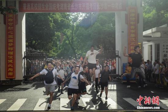 资料图:2018年湖南长沙一考点外,考生们跑出考场,庆祝高考结束。中新社记者 杨华峰 摄