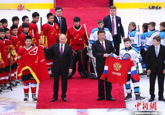 资料图:2018年6月8日晚,中国国家主席习近平同俄罗斯总统普京在天津共同观看中俄青少年冰球友谊赛。两国元首同小队员们亲切交谈、合影,并共同为比赛开球。 中新社记者 刘震 摄