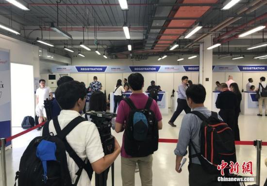 """6月10日,新加坡为""""金特会""""而设在F1维修大楼的国际媒体中心正式开放,多国媒体记者陆续抵达媒体中心等待注册,领取记者证。 中新网记者 孟湘君 摄"""