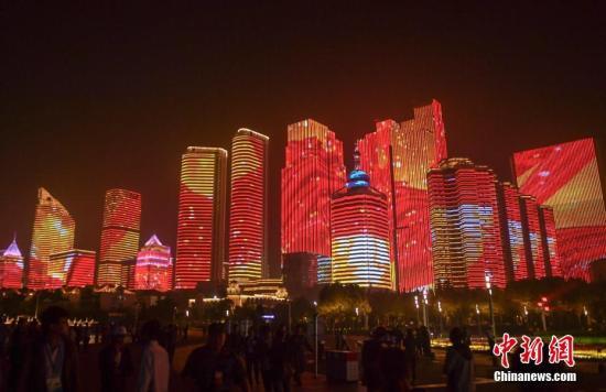 6月9日晚,民众出门观看上海合作组织青岛峰会在青岛举行的灯光焰火艺术表演。 中新社记者 张勇 摄