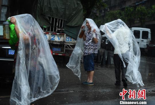 资料图:重庆主城突降暴雨 街头民众自制雨衣避雨图为民众用塑料袋制作的雨衣。 陈超 摄