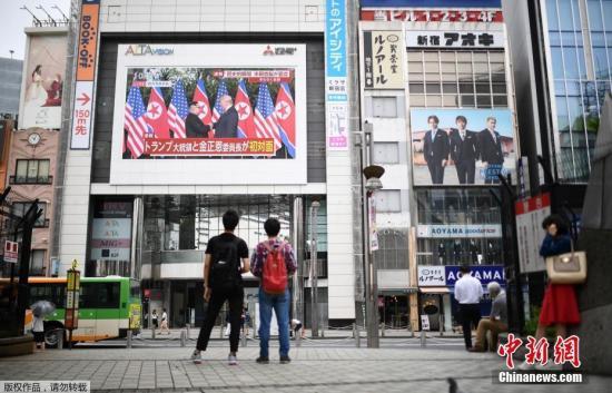 資料圖:2018年6月,在日本東京的一個廣場,人們通過戶外大屏幕觀看朝美領導人首次會晤的直播畫面。