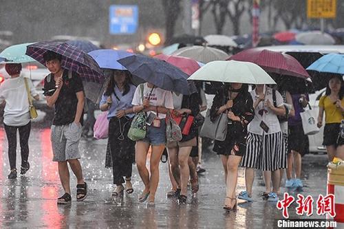 广州民众在暴雨中出行。 中新社记者 陈骥 摄