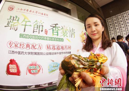 资料图:端午节将至,江西省中医院工作人员身着古装,手捧香囊,向市民介绍中药香囊的作用和功效。王昊阳 摄
