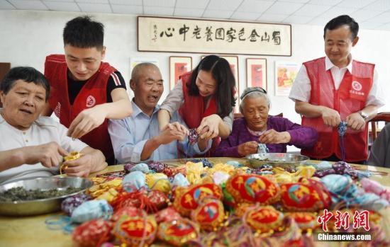 6月15日,志愿者和老人一起制作香囊。当日,安徽省合肥市南岗镇新城社区志愿者来到蜀山区金色家园养老中心,为100多位老人送来粽子,并与他们一起扎香囊,共迎端午。中新社记者 韩苏原 摄