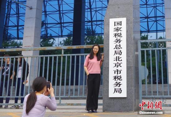 6月15日,新组建的国家税务总局北京市税务局正式挂牌成立,标志着原北京市国家税务局、北京市地方税务局正式合并。今年3月中共中央印发《深化党和国家机构改革方案》,提出将省级和省级以下国税地税机构合并,具体承担所辖区域内各项税收、非税收入征管等职责。图为民众在新牌前拍照。<a target='_blank' href='http://www.chinanews.com/'>中新社</a>记者 贾天勇 摄