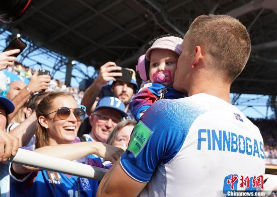 赛后,冰岛球员抱家人庆祝。 中新社记者 毛建军 摄