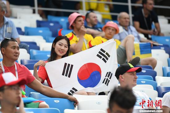 赛前,看台上的美女球迷手持韩国国旗。<a target='_blank' href='http://www.chinanews.com/'>中新社</a>记者 田博川 摄