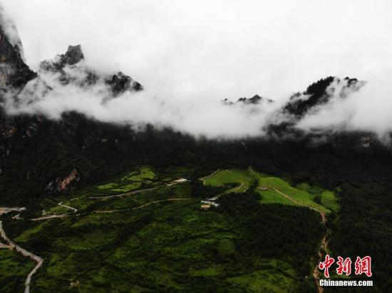 """资料图:甘肃藏地扎尕那云雾缭绕似仙境。扎尕那是位于甘肃省甘南藏族自治州迭部县西北30余公里处的益哇乡的一座古城,藏语意为""""石匣子""""。杨艳敏 摄"""