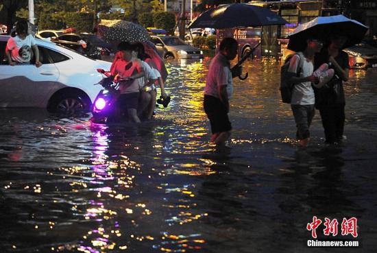 福州市民在积水中出行。 张斌 摄
