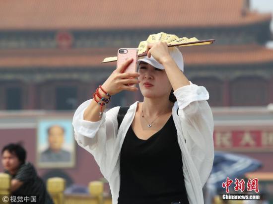 资料图:北京,天安门广场游客遮阳防晒各有各招。图片来源:视觉中国