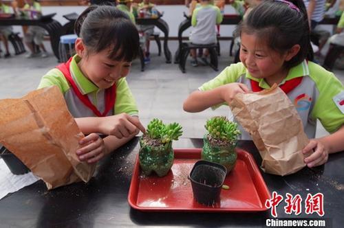 """6月27日,北京市顺义区的小学生在环保实践课上用废旧塑料瓶种植物。当日,2018""""我们在乎,源于本身――就(旧)凭(瓶)你有用环保行动""""在京启动,活动由中粮可口可乐饮料(北京)有限公司等发起,旨在让北京的社区和中小学校园中有更多人了解和认识废旧饮料瓶安全回收和再利用的重要性。/p中新社记者 贾天勇 摄"""