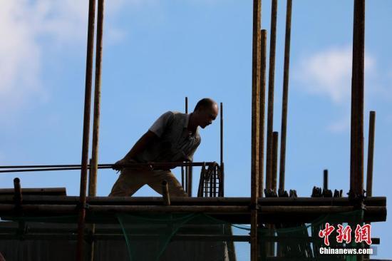 工人在搬运建筑材料。肖晨威 摄