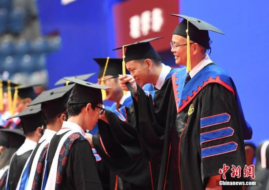6月30日,大学老师们正在为毕业生们整理学士帽。当日,浙江大学6000余名本科生正式毕业,告别校园,并以拍照等形式纪念毕业。中新社记者 王刚 摄