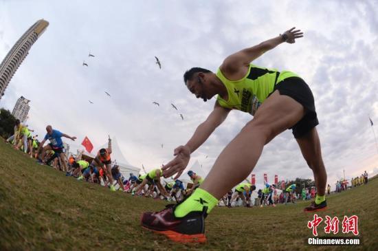 资料图片:华人参加2018澳大利亚黄金海岸马拉松。图为赛前热身。中新社记者 杜洋 摄