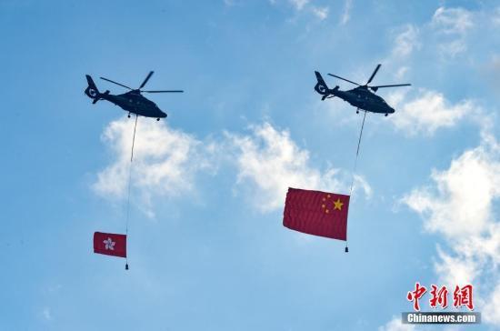 7月1日,香港特别行政区政府在金紫荆广场举行隆重的升旗仪式,庆祝香港回归21周年。图为两架直升机悬挂五星红旗和香港区旗经过金紫荆广场上空。<a target='_blank' href='http://www.chinanews.com/'>中新社</a>记者 张炜 摄