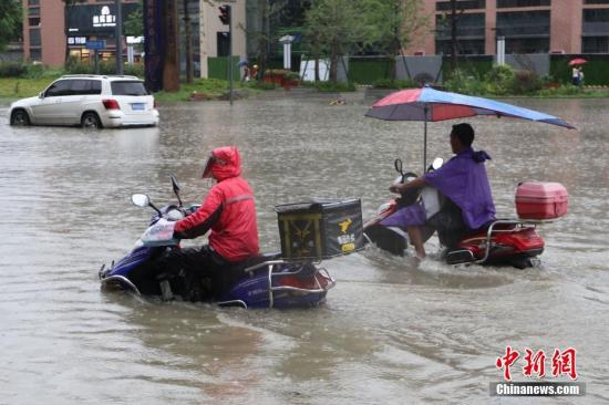 资料图:成都遭遇暴雨,骑行者行驶在积水路面。张浪 摄
