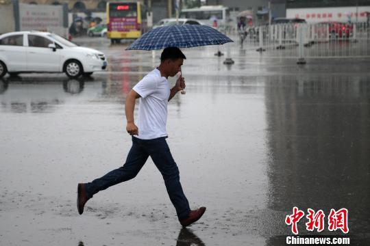 资料图:民众雨中追赶公交车。 张远 摄