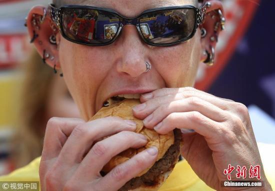 """当地时间2018年7月3日,美国华盛顿举办年度吃汉堡""""大胃王""""比赛,迎接独立日。世界排名第一的""""大胃王""""Molly Schuyler参加,她在10分钟内吃了27个汉堡,再次赢得比赛。图片来源:视觉中国"""