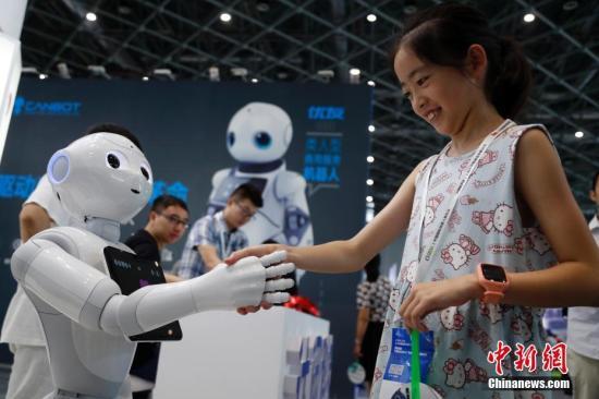 资料图:一位女孩在和机器人握手交谈。汤彦俊 摄