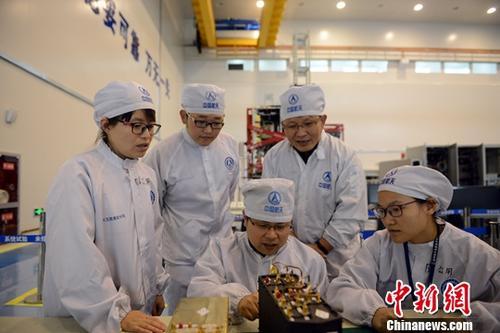 图为张立新(坐者左1)同团队研究人员在研制北斗导航卫星有效载荷过程中研讨交流。发 刘杰 摄