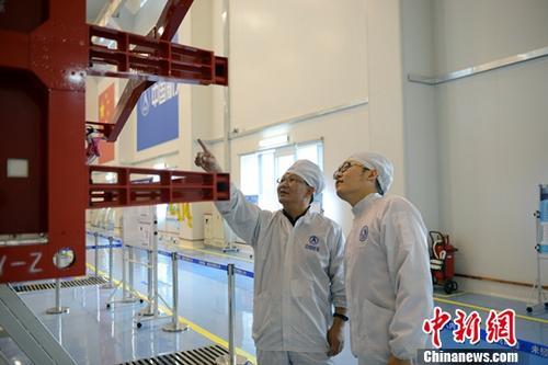 图为张立新(左)同团队研究人员在研制厂房中交流。中新社发 刘杰 摄