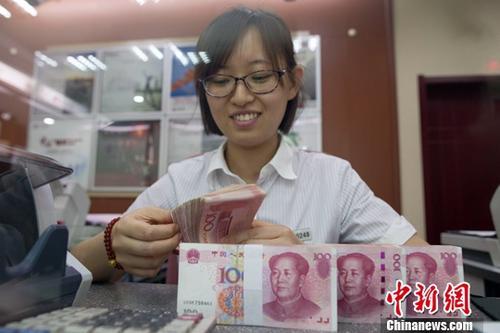 7月5日,山西太原一银行工作人员正在清点货币。人民币对美元汇率中间价在经历了过去11个交易中的10次下调后终于迎来大涨。5日,中国外汇交易中心公布人民币对美元汇率中间价报6.6180,较前一交易日大幅上调415个基点,创下自2017年10月11日以来的最大升幅。中新社记者 张云 摄