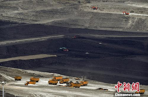 7月4日,位于新疆准东经济技术开发区,新疆天池能源有限责任公司所属的南露天煤矿,大型运输车辆正在深达200米左右的矿坑中忙着转运原煤。准东煤田位于新疆准格尔盆地东部,东西长达220公里的茫茫戈壁下蕴藏着3900亿吨煤炭资源,已探明储量2149亿吨,是中国目前最大的整装煤田。准东煤田包括五彩湾、大井、将军庙、西黑山、老君庙5个矿区,其中4个矿区规划已取得国家批复。 中新社记者 刘新 摄