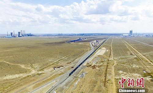 资料图:2018年7月4日16时20分,一列由216只敞顶箱组成全长1600米、满载煤炭、总重达万吨的列车自新疆乌准铁路准东站缓缓开出。中新社记者 刘新 摄
