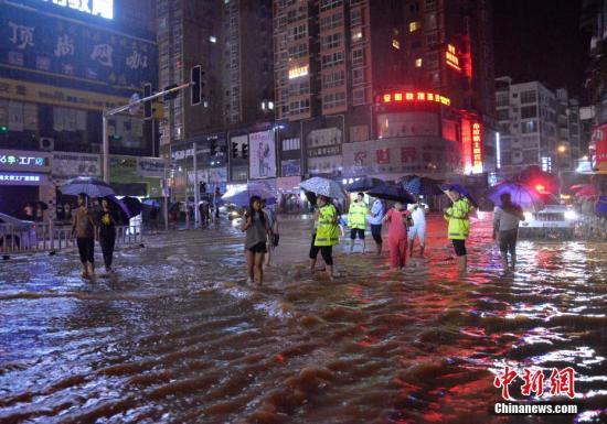 7月6日上午,民众淌水过街。当日,贵州省铜仁市松桃苗族自治县遭遇暴雨袭击。<a target='_blank' href='http://www.chinanews.com/'>中新社</a>发 龙元彬 摄