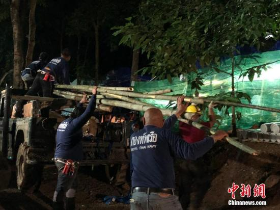 7月5日傍晚,在救援营地,救援人员卸下运来的竹子,准备制作竹筏用于援救被困人员出洞。当天,泰国清莱13名被困洞穴少年足球队成员的救援工作正在持续紧张进行。 中新社记者 王国安 摄