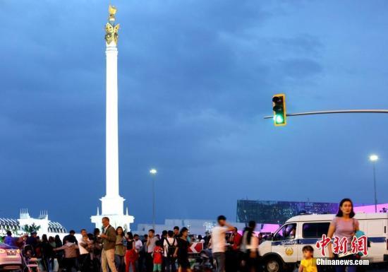 """7月6日,哈萨克斯坦迎来第20个首都日。图为当天阿斯塔纳""""哈萨克耶勒""""纪念碑前举行大型演出庆祝建都20周年,众多市民前往观看。 中新社记者 文龙杰 摄"""