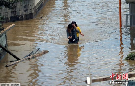 据日媒报道,8日,日本警方和自卫队继续在暴雨灾情严重的冈山、广岛和爱媛各县等搜寻失联者。截至目前,死亡人数已升至总计70人。图为仓敷市街道被水淹没,两名女子在水中跋涉。