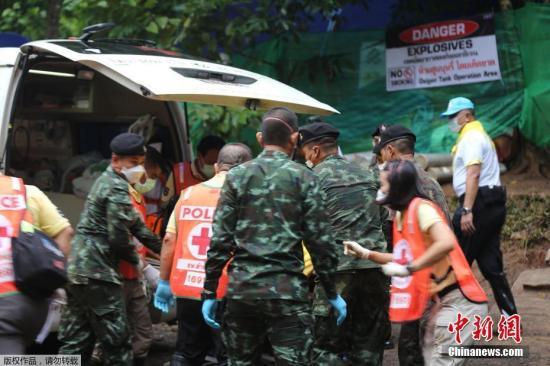 图为7月8日,救援人员将获救少年送上救护车。