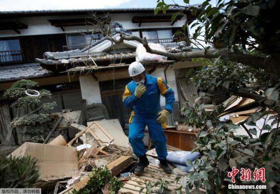 当地时间7月9日,日本冈山县仓敷马比镇,一名警察在检查房屋受损情况。