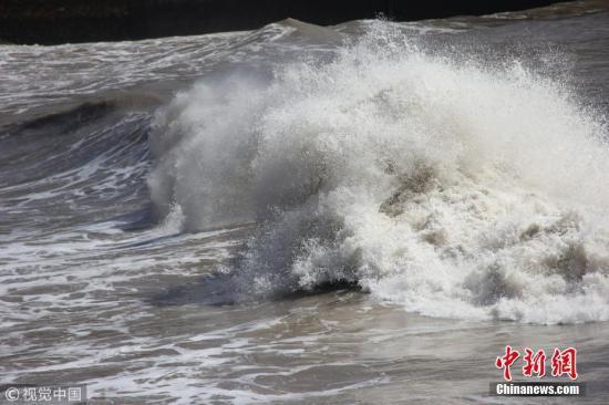 """7月10日,随着超强台风""""玛莉亚""""的逼近,浙江温岭石塘镇海域风高浪急,当地沿海金沙滩景区一边组织人员装运沙包抗台预防,一边实施景区关闭,确保游客安全。金云国 摄 图片来源:视觉中国"""