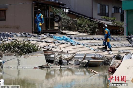 资料图:当地时间7月9日,日本冈山县仓敷马比镇,警察在检查房屋受损情况。