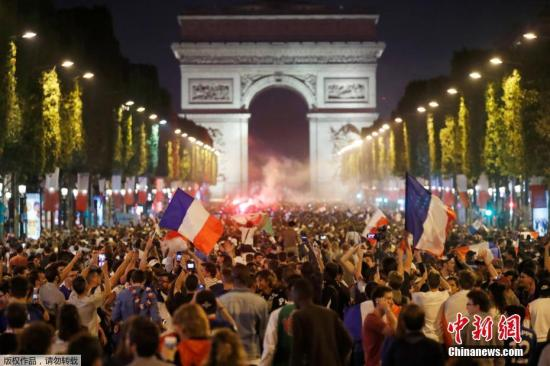 法国球迷们手持照明弹和旗帜庆祝在巴黎街头、凯旋门进行庆祝。