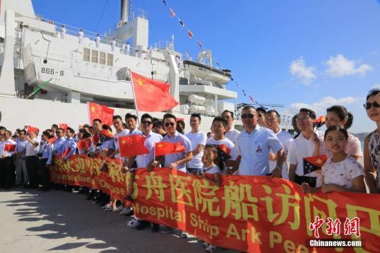 """当地时间7月11日10时许,执行""""和谐使命-2018""""任务的中国海军和平方舟医院船驶抵莫尔斯比港,开始对巴布亚新几内亚进行为期8天的友好访问并提供人道主义医疗服务。这是和平方舟时隔4年再次到访巴新。图为巴布亚新几内亚莫尔斯比港码头上,华人华侨挥动国旗欢迎中国海军和平方舟医院船访问。<a target='_blank' href='http://www.chinanews.com/'>中新社</a>发 史奎吉 摄"""