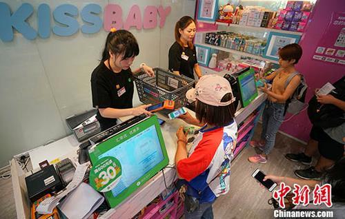 7月12日,内地年轻顾客在香港屯门一家母婴用品商店用微信支付付款。<a target='_blank' href='http://550df.com/'>中新社</a>记者 张炜 摄