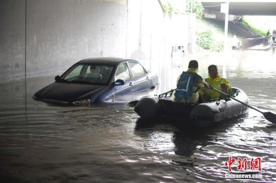 资料图:北京暴雨,救援人员乘救生艇开展搜救作业。中新社记者 贾天勇 摄
