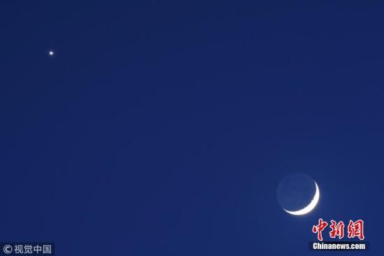 """当地时间2018年7月15日,哥伦比亚波哥大的夜空中,出现了""""金星伴月""""奇观。 图片来源:视觉中国"""