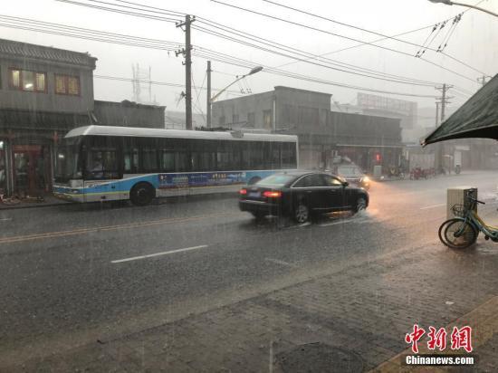 车辆、行人在大雨中穿行。 张楷欣 摄