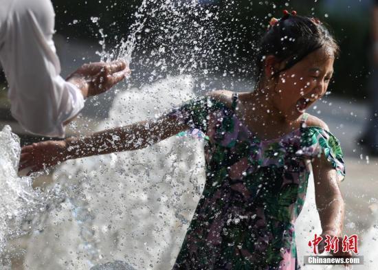 7月17日,小朋友在南京街头一处喷水池中戏水。中新社记者 泱波 摄